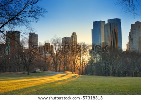 Central Park, New York City, with skyscrapers,snow and sunset - stock photo