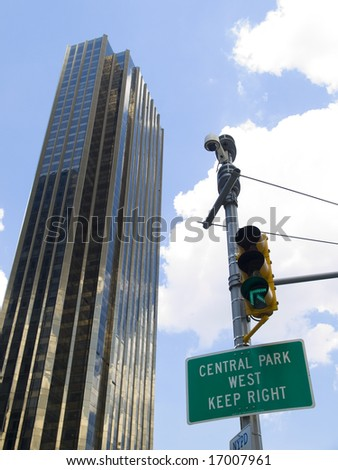 Central Park West sign hanging on a traffic light beside a skyscraper in a cloudy blue sky background. - stock photo