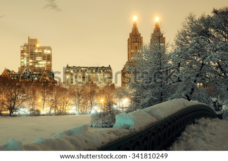 Central Park winter with skyscrapers and Bow Bridge in midtown Manhattan New York City - stock photo