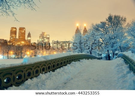 Central Park winter with skyscrapers and Bow Bridge in midtown Manhattan New York City