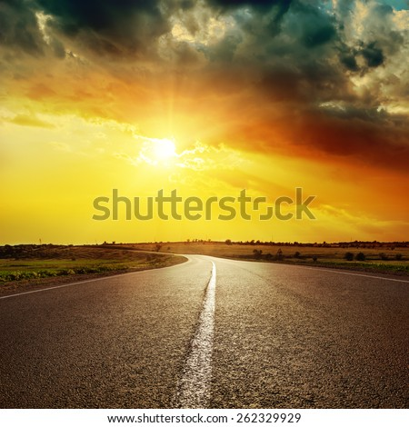 central white line on asphalt road and dramatic sunset - stock photo