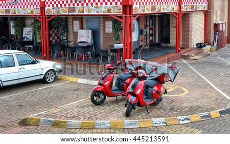 Centurion, Johannesburg, South Africa - January 6, 2014: Red motorcycles are ready for delivery of delicious South African take-away dishes for you from a cafe in Centurion in South Africa.