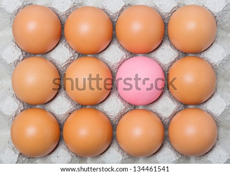 Century egg among chicken eggs on paper tray - stock photo