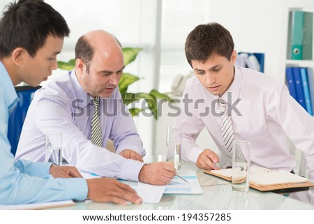 Ceo discussing report with his young colleagues - stock photo