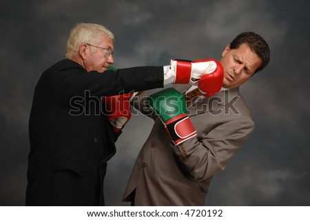 CEO punching another businessman in the jar with boxing gloves - stock photo