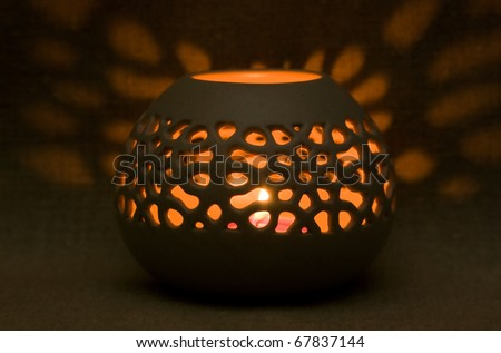 Ceramic aroma lamp in the dark on the burlap background - stock photo