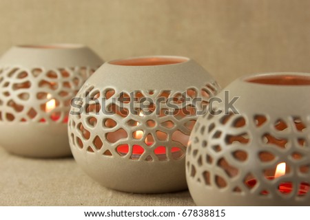 Ceramic aroma lamps with small red burning candles on the burlap background - stock photo