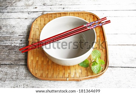 ceramic bowl and chopsticks in bamboo tray on wooden table. , - stock photo