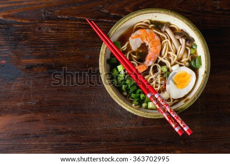 Ceramic bowl of asian ramen soup with shrimp, noodles, spring onion, sliced egg and mushrooms, served with red chopsticks over dark wooden surface. Top view - stock photo