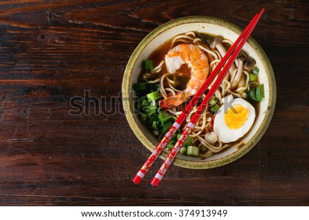 Ceramic bowl of asian ramen soup with shrimp, noodles, spring onion, sliced egg and mushrooms, served with red chopsticks over dark wooden surface. Flat lay