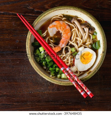Ceramic bowl of asian ramen soup with shrimp, noodles, spring onion, sliced egg and mushrooms, served with red chopsticks over dark wooden surface. Top view. Square image - stock photo
