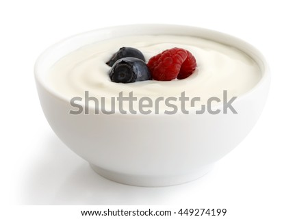 Ceramic bowl of white yogurt with berries isolated on white background.