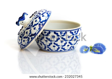 Ceramic bowl on white with natural shadow and blue herp flowers