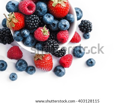 Ceramic bowl with blueberries, strawberries and blackberries on white background. Close up, high resolution product. Harvest Concept - stock photo