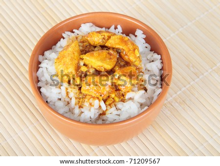 Ceramic bowl with rice and chicken in curry - stock photo