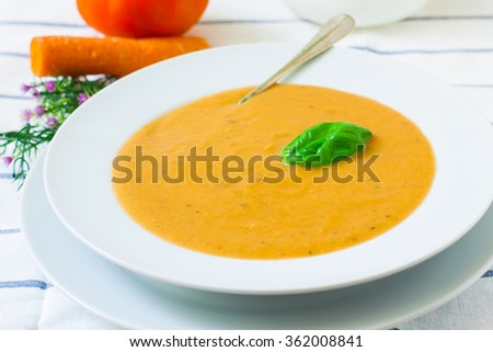 ceramic bowl with vegetables cream and basil - stock photo