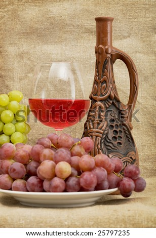 Ceramic brown bottle, grapes and red wine on canvas