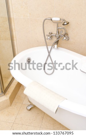 Ceramic classic bathtub in luxurious hotel bathroom - stock photo
