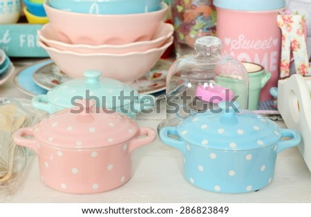 Ceramic cocottes and dishware in pastel colors - stock photo