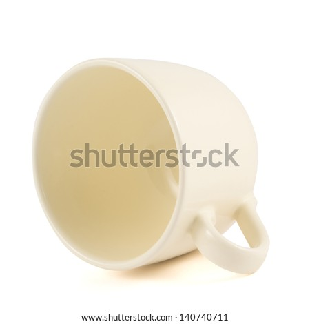 Ceramic cream colored cup lying on its side isolated over white background - stock photo