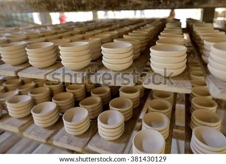 Ceramic cup in rack prepare for bring in furnace in factory - stock photo