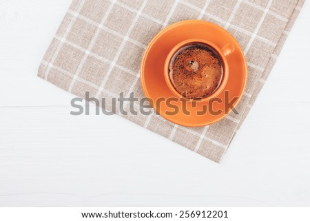 Ceramic cup of coffee lying on squared napkin on white wooden table with place for text - stock photo