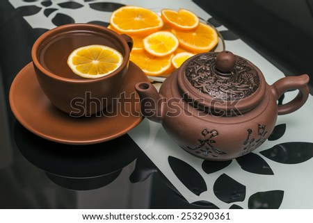 ceramic cup of tea and tea pot with  lemon on glass kitchen table - stock photo