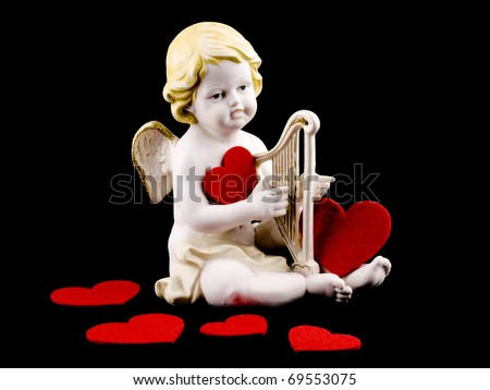 Ceramic cupid figure with felt red heart on black background - stock photo