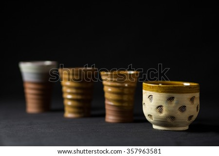 Ceramic cups in series with paw cup in the foreground - stock photo