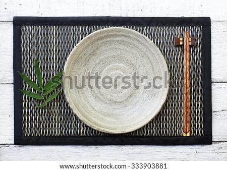 ceramic dish (plate) and chopsticks on bamboo mat.Flat lay - stock photo