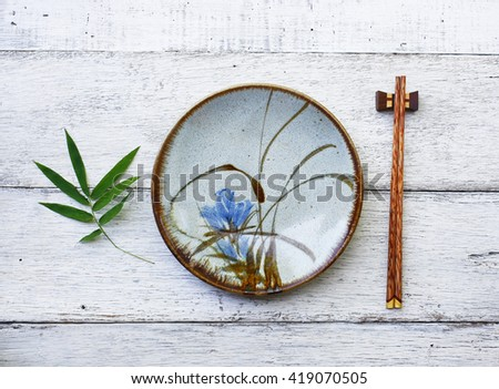 ceramic dish (plate) and chopsticks on white wooden table.Flat lay - stock photo