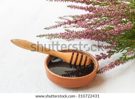 Ceramic dish with honey , dipper and branches of heather - stock photo