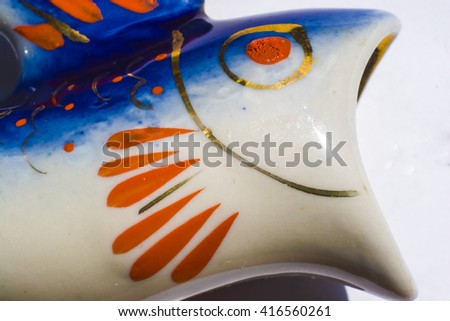 Ceramic figurine, papier-mache in a shape of a fish head, painted with a blue, red and golden colors. - stock photo
