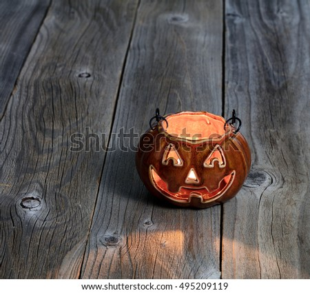 Ceramic glowing pumpkin decoration on rustic wooden boards