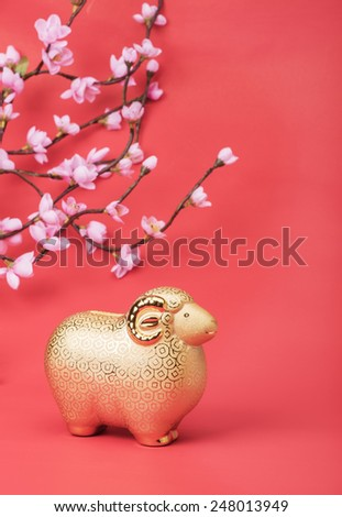 Ceramic goat souvenir on red paper,2015 is year of the goat - stock photo