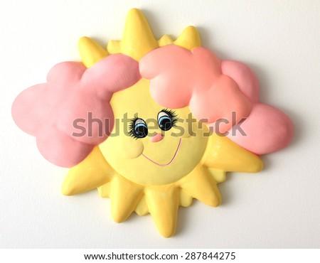 Ceramic happy smiling sunshine face ornament.  - stock photo