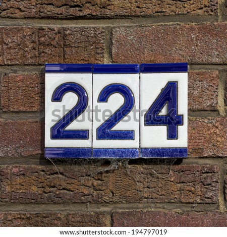 ceramic house number two hundred and twenty four, on three separate tiles. - stock photo