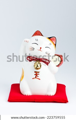 Ceramic Japanese welcoming Cat or lucky Cat ( Maneki Neko ) - stock photo