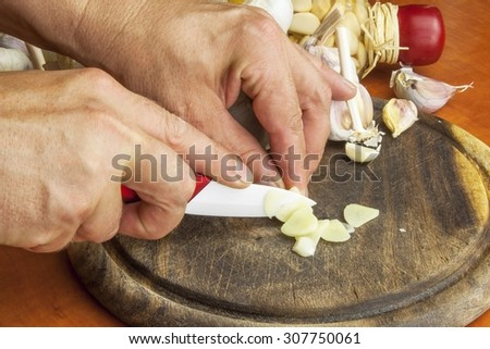 Ceramic knife chopping garlic preparation cooking. Garlic, aromatic ingredients for flavoring food. Home remedy for colds and flu. Preparing for the garden party and barbecue meat