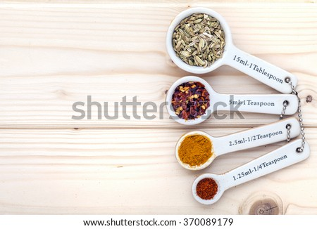 Ceramic measurement spoons filled with various spices on a pinewood background linked together and viewed from above.