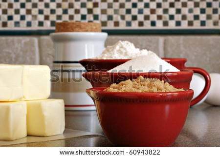 Ceramic measuring cups filled with flour and sugar along with eggs and butter on kitchen counter.  Macro with shallow dof. - stock photo