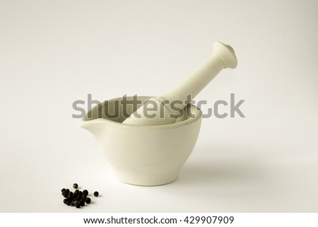 Ceramic mortar and pestle with black peppercorns against white background - stock photo