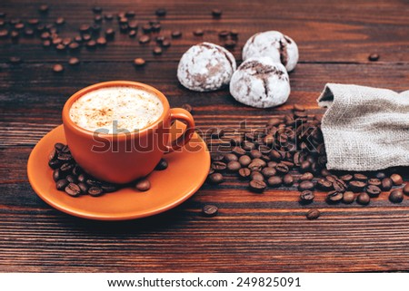 Ceramic orange cup of coffee with foam, with cookies and coffee beans, standing on wooden table - stock photo