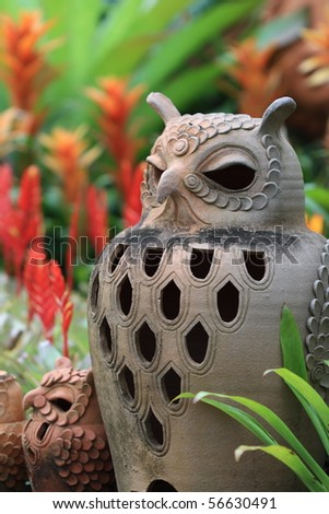 ceramic owl in the natural park with orange bromeliad back ground - stock photo