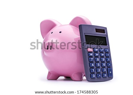 Ceramic pink piggy bank with a calculator leaning up against it over a white background conceptual of finances, money and investment