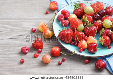 Ceramic plate of assortment berries strawberries, raspberries, cherries at old wooden table. Close up, high resolution product. Harvest Concept - stock photo