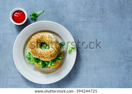 Ceramic plate with cheese sandwich on bagel with cucumber and lettuce over grey vintage background, border, top view, copy space. Vegetarian and healthy eating concept.  - stock photo