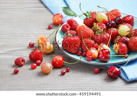Ceramic plate with mixed berries at old wooden table. Close up, high resolution product. Harvest Concept - stock photo