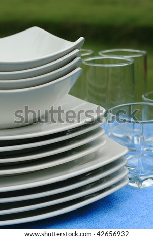 Ceramic plates and glassware set on beach towels at resort - stock photo