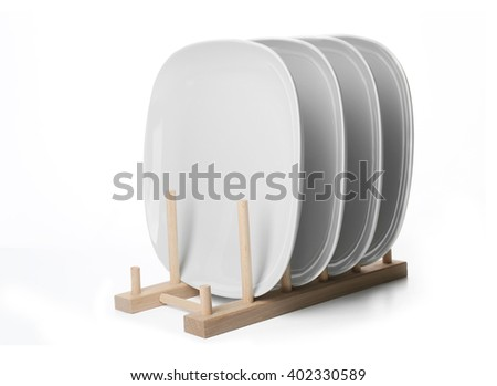 Ceramic plates in wooden stand, isolated on white - stock photo